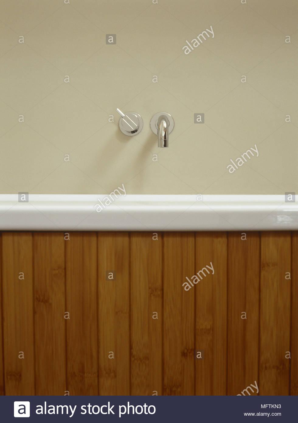 A detail of a modern bathroom bath with wood surround chrome taps ...