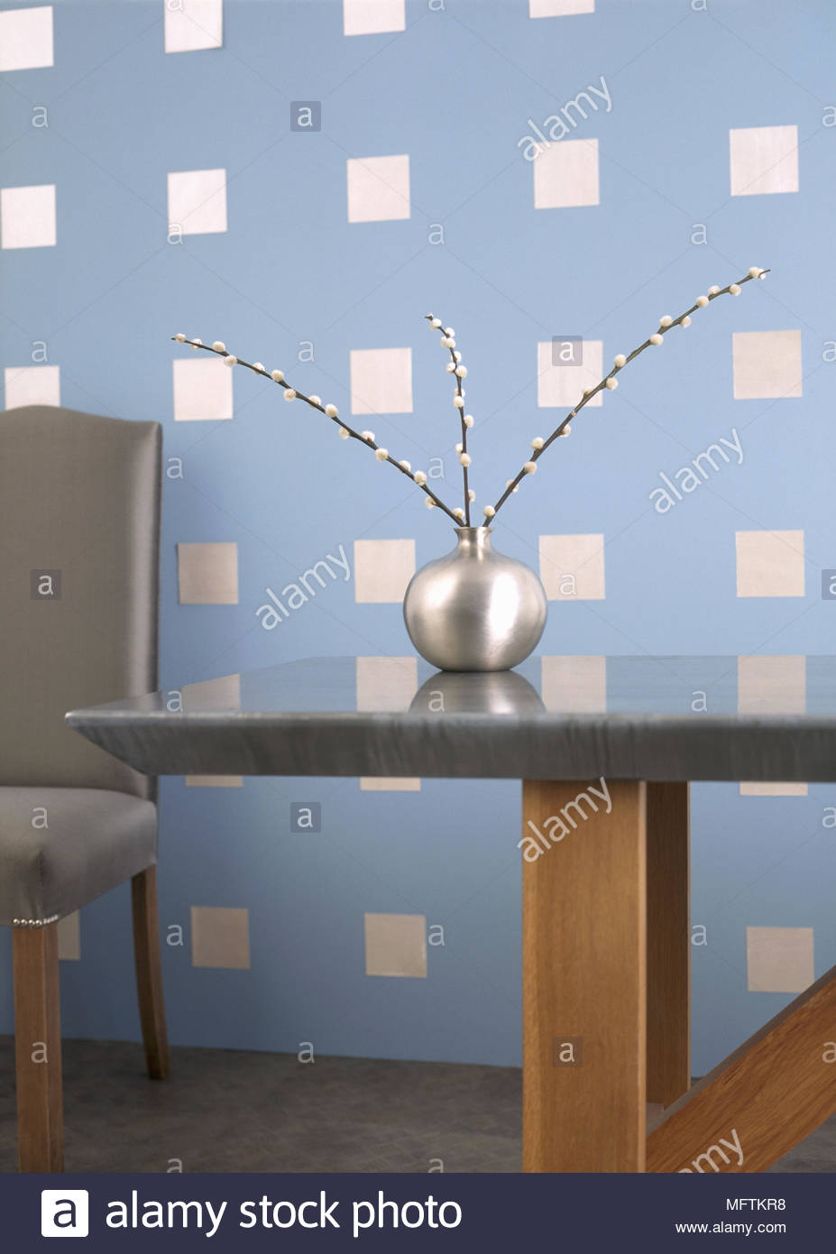 A Detail Of Modern Dining Room With Square Pattern Paint Effect On Wall Marble Top Table Upholstered Chair Silver Steel Vase Twig Arrangement