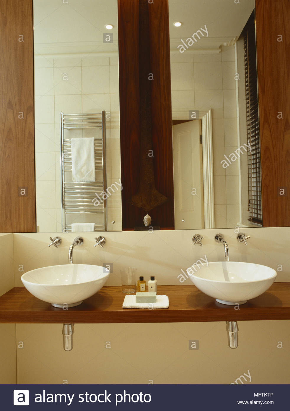 A detail of a modern neutral bathroom twin washbasins set on wooden ...