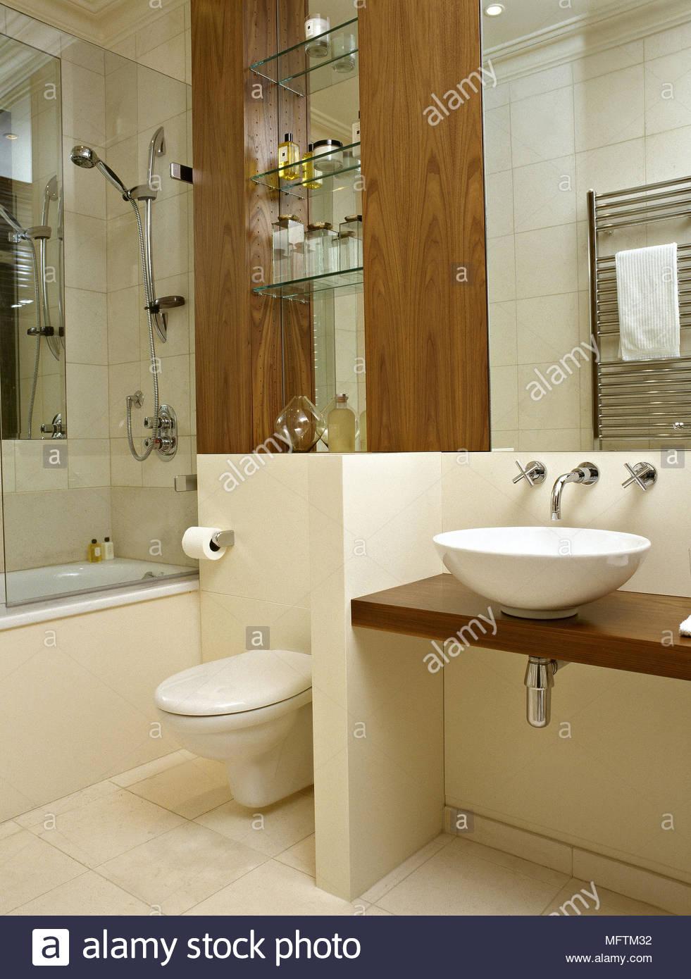 A modern bathroom in neutral tones shower over bath bowl washbasin ...