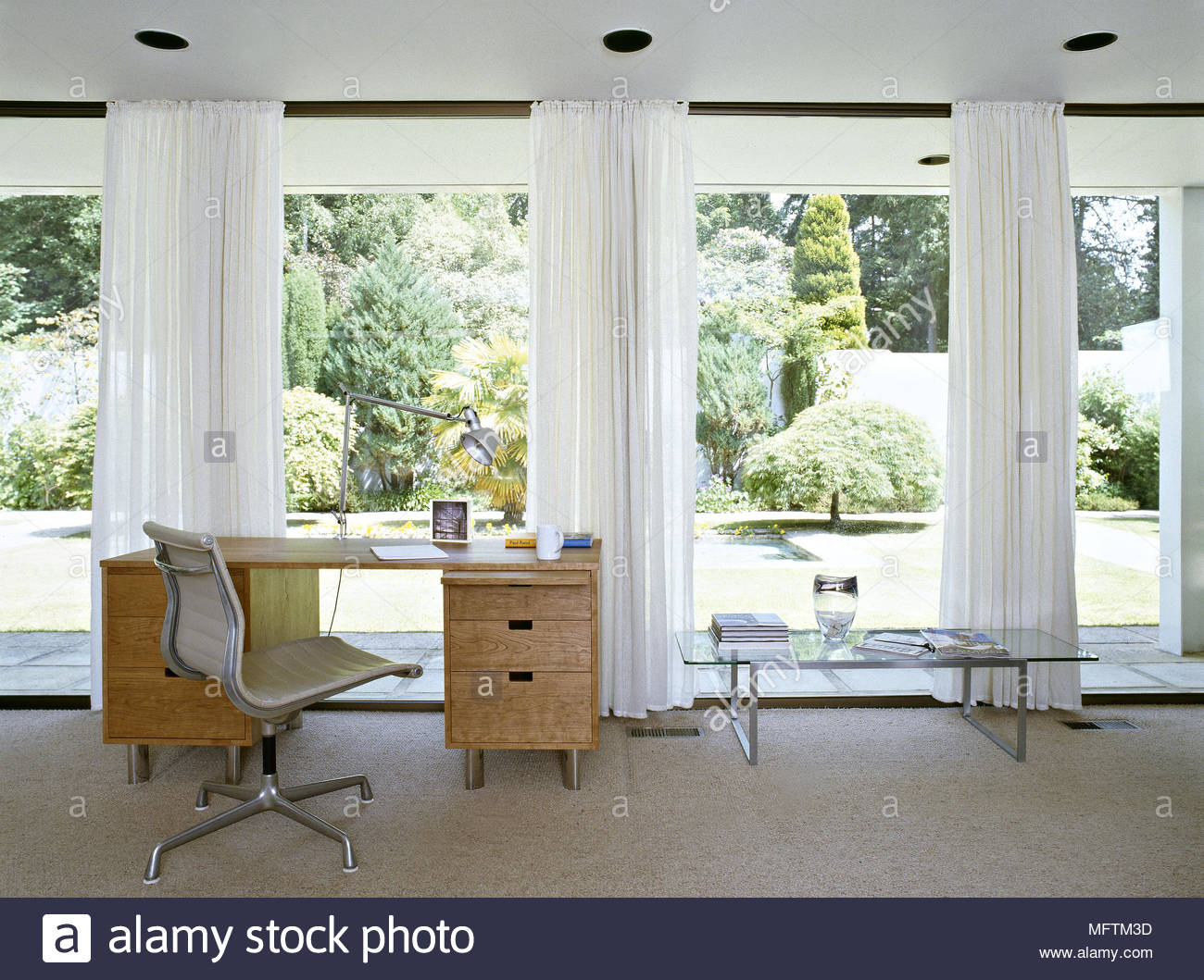 A Modern Home Office With Wooden Desk Swivel Chair Windows With White  Curtains Glass Coffee Table