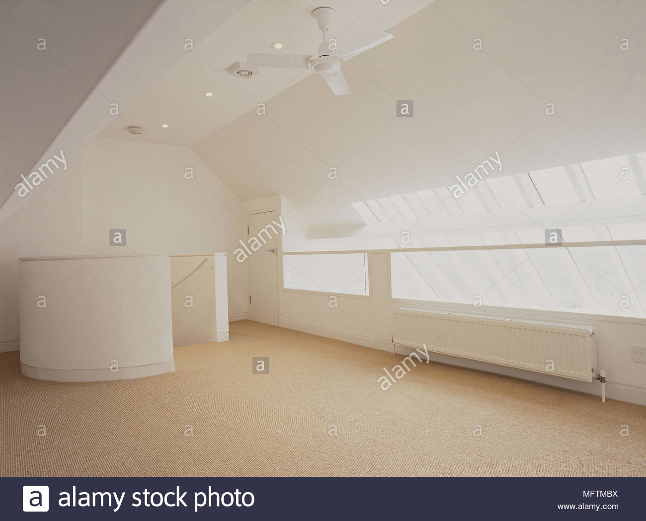 Ceiling light with fan moving stock photos ceiling light with fan carpeted and empty loft apartment with glass panelled windows and ceiling fan stock image aloadofball Choice Image