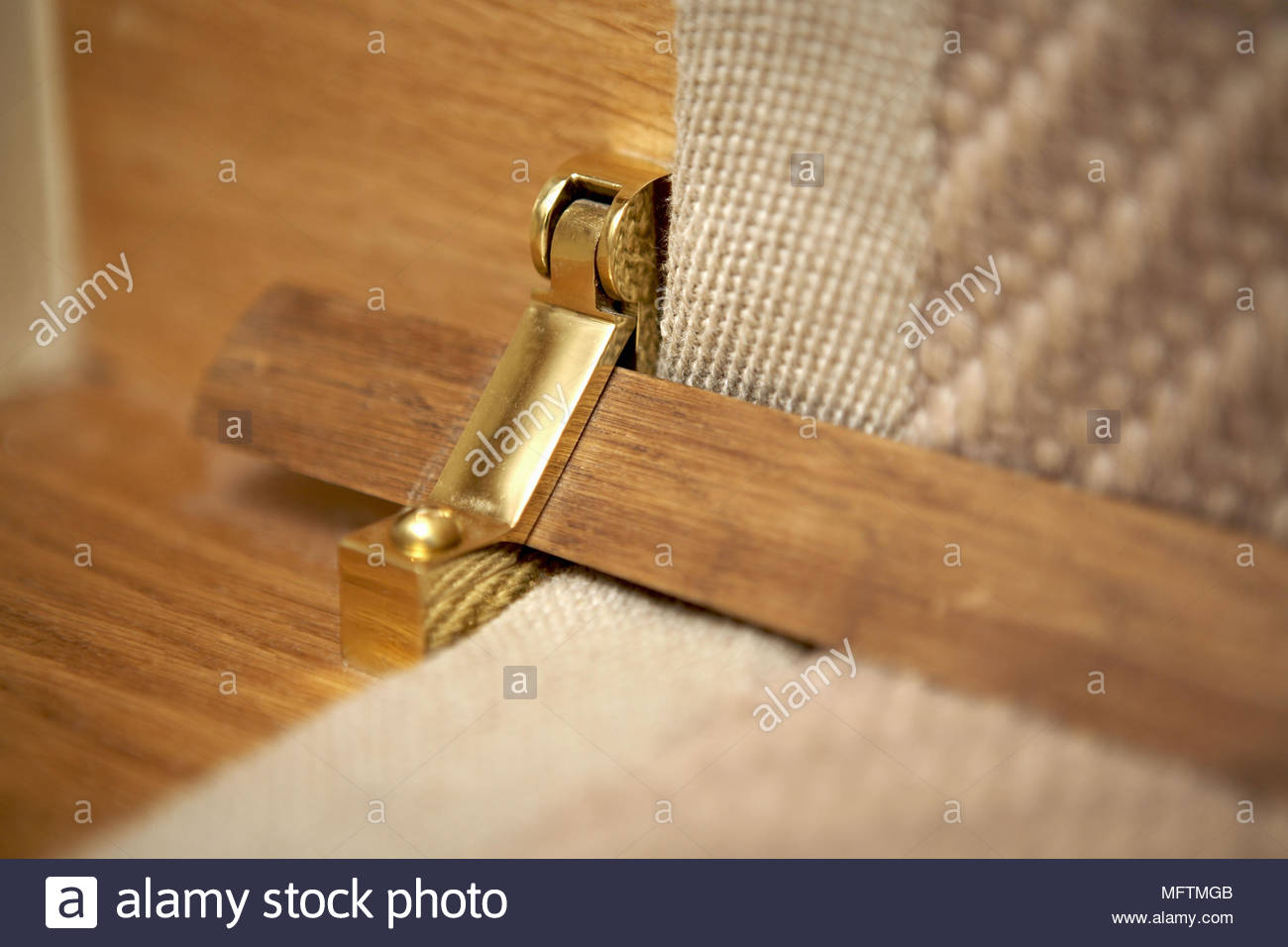 Close Up Of Traditional Wooden Stair Rod Kept In Place With Brass Clip
