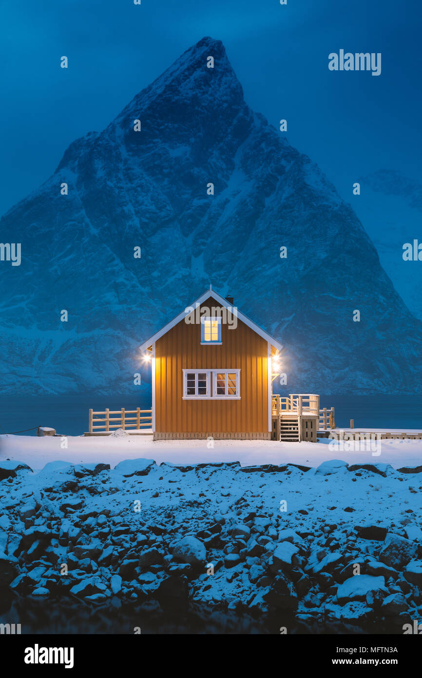 Traditional yellow Rorbu cabin with Olstinden mountain peak at twilight in winter, village of Sakrisoy, Lofoten Islands archipelago, Norway - Stock Image