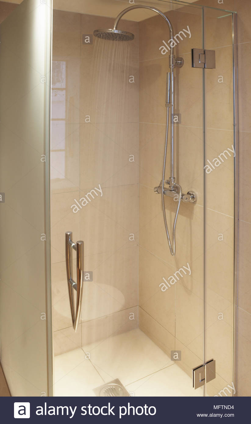 Glass shower cubicle with running water from curved metal shower ...