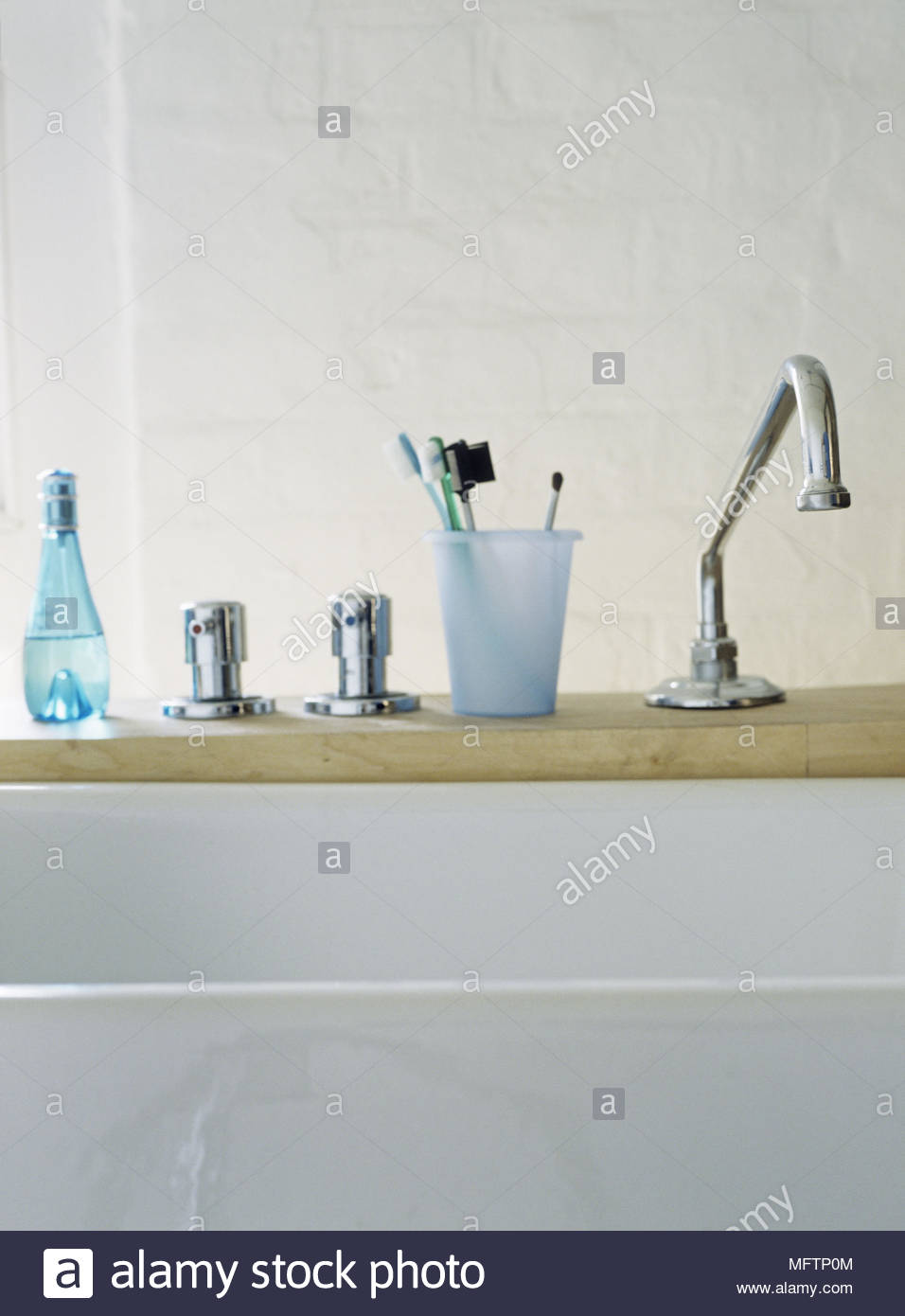 Line of five objects on a wooden bathroom shelf including ...