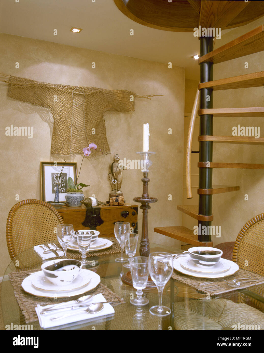 Country Dining Room With Textured Plaster Walls, Floating Spiral Staircase,  And A Glass Top Dining Table With Wicker Chairs.