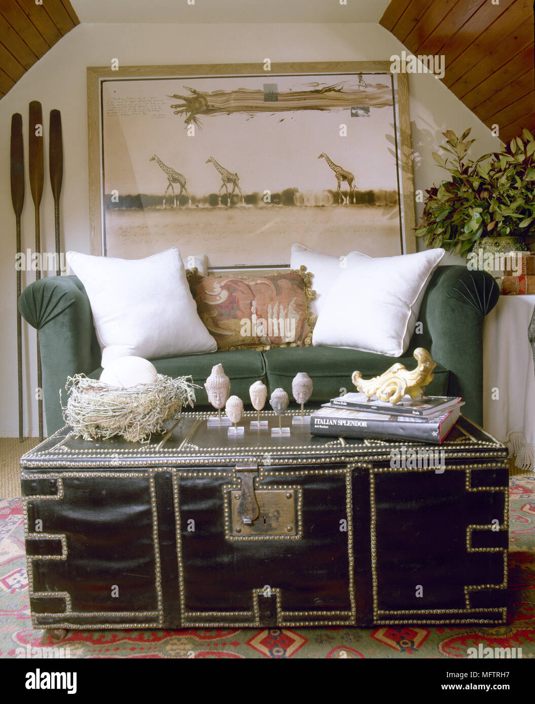 Exotic Sitting Room With A Sloping, Wood Panelled Ceiling, Sofa, Trunk  Coffee Table, And Safari Artwork.