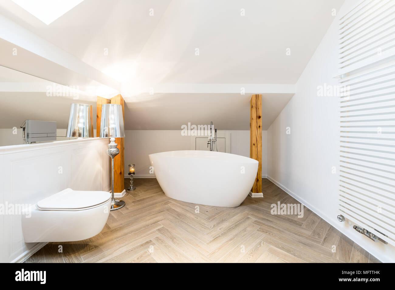 Modern, white attic bathroom interior with oval, ceramic bathtub ...