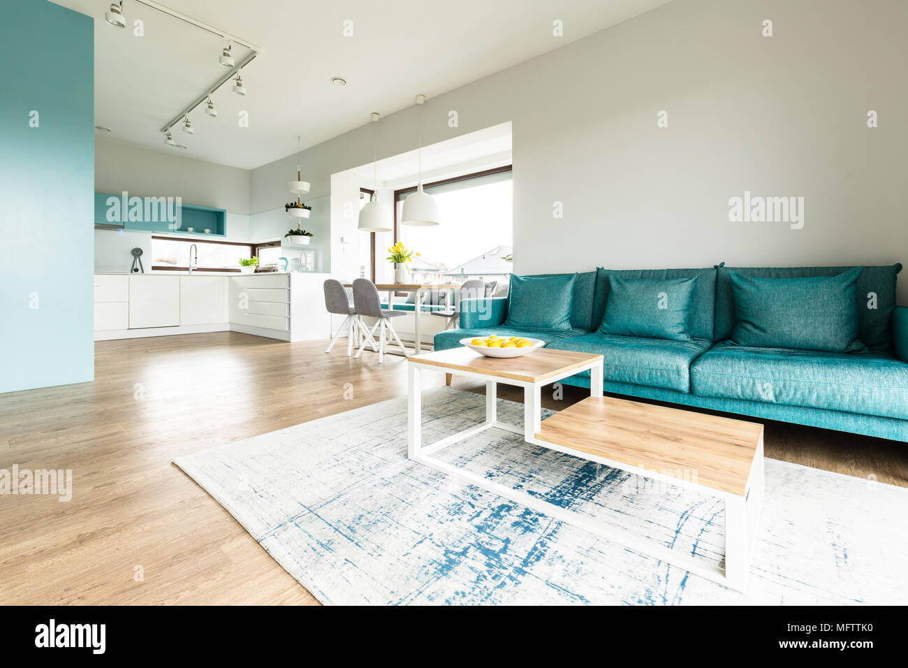 White and turquoise open space house interior with big sofa modern kitchen and a dining table by large windows