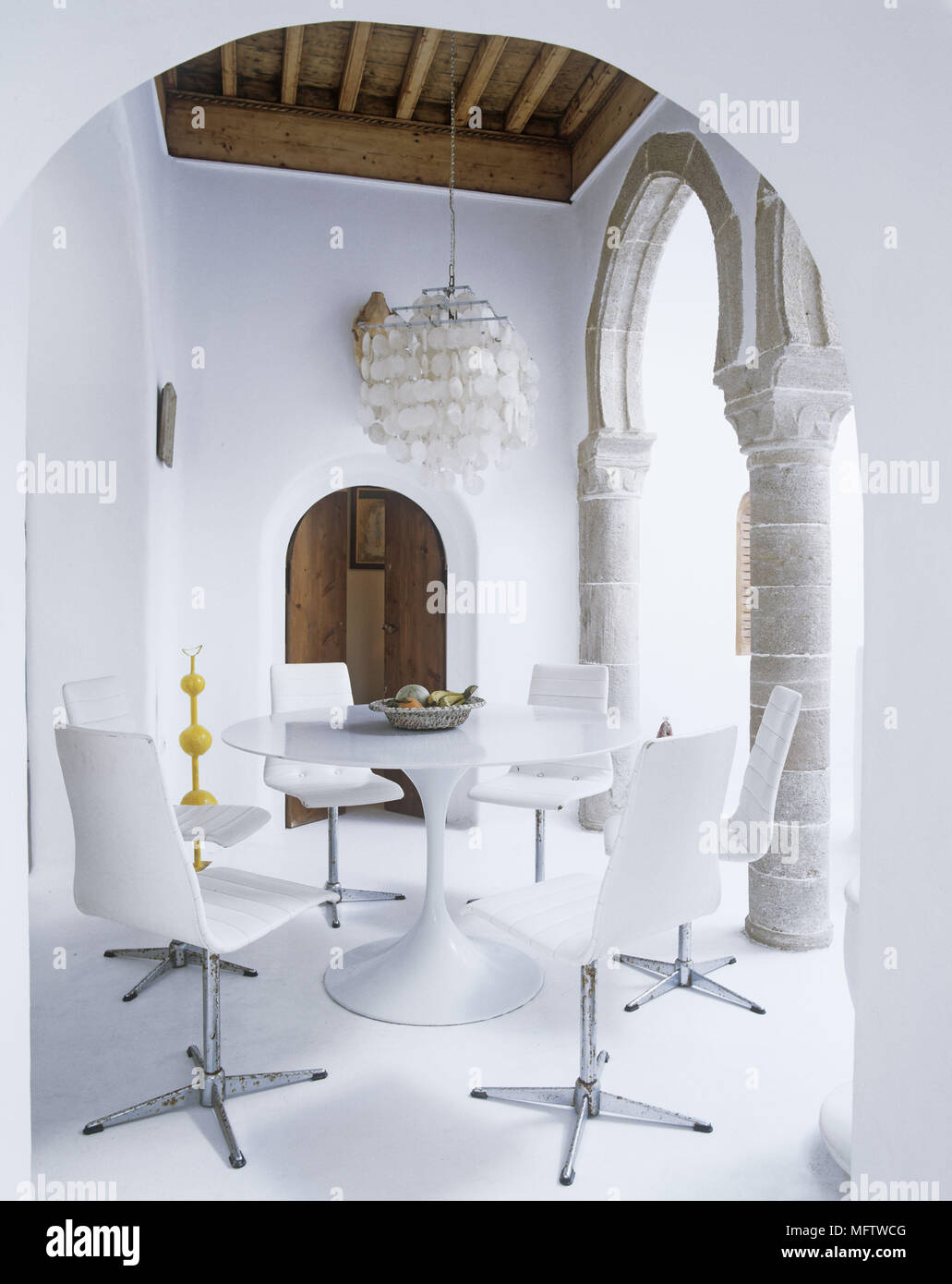 A Rustic Whitewashed Dining Room Stone Moroccan Archways Contrast With  Modern Retro White Plastic Table And Chairs
