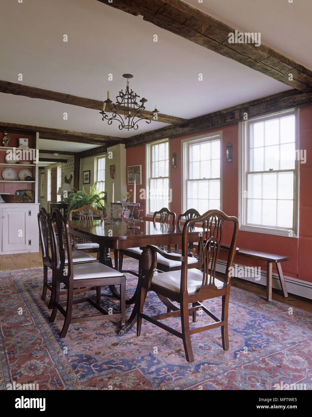 A Traditional Dining Room With Wooden Table And Chairs On Large Oriental Rug Metal Chandelier Hanging From Beam