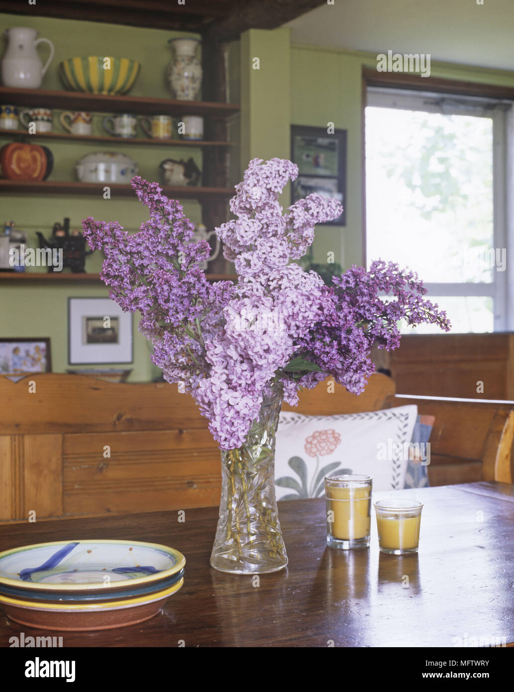 Details of a vase of purple flowers on a wooden dining table with a plate and two candles. Stock Photo