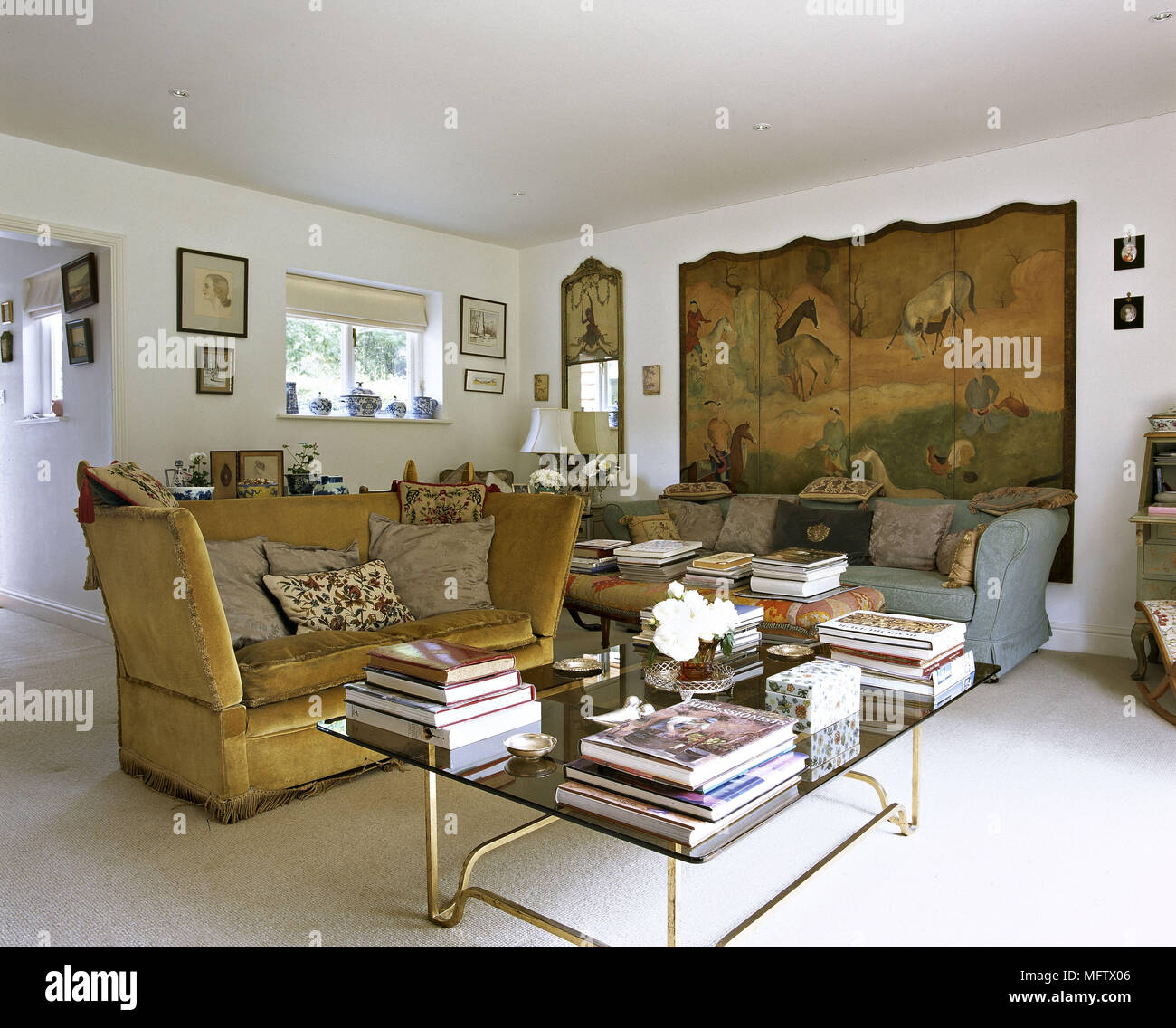 High back sofa and glass coffee table stacked with books in sitting room