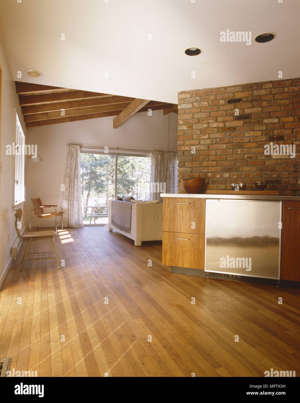 Open plan kitchen leading through to sitting room with wooden flooring and ceiling and bare brick wall Stock Photo