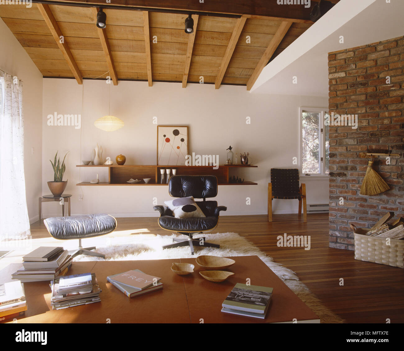 Sitting room with bare brick wall stained floorboards wooden ceiling and Charles Eames chair Stock Photo