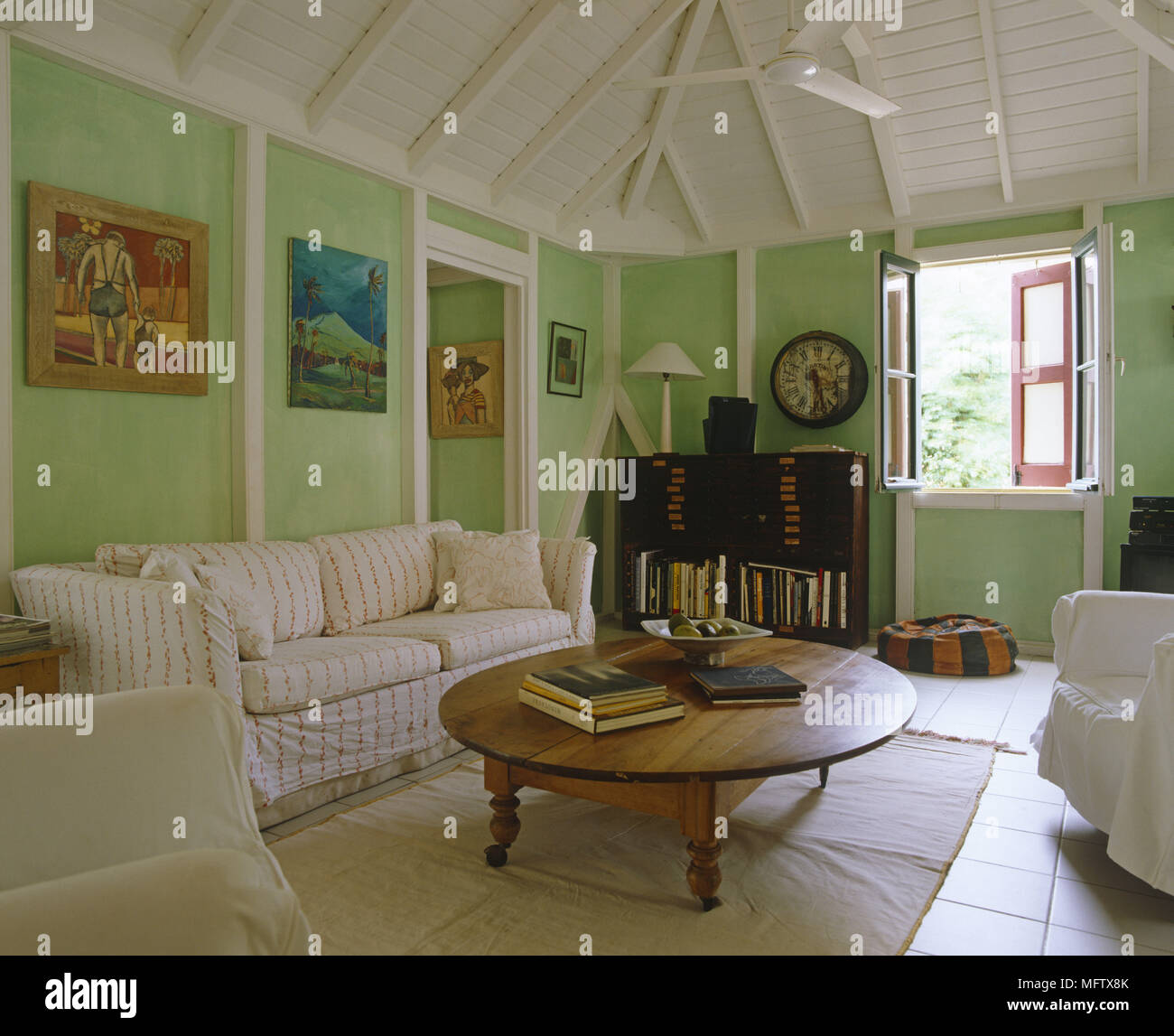 Sitting room with tiled floor wooden ceiling and armchairs with paintings on the wall Stock Photo