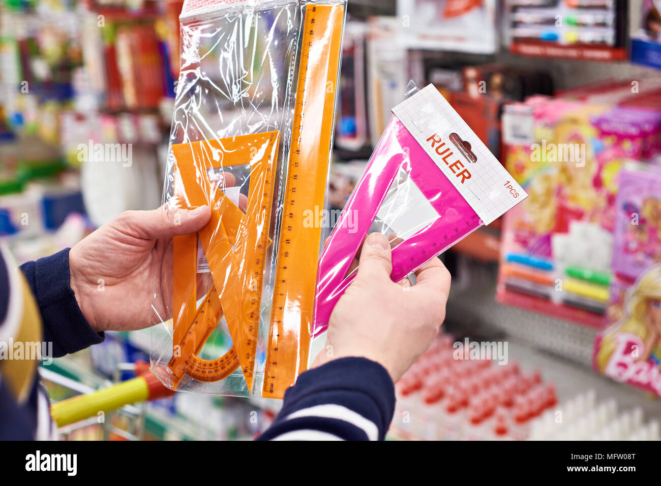 Buyer selects plastic rulers and angles in the stationery store - Stock Image
