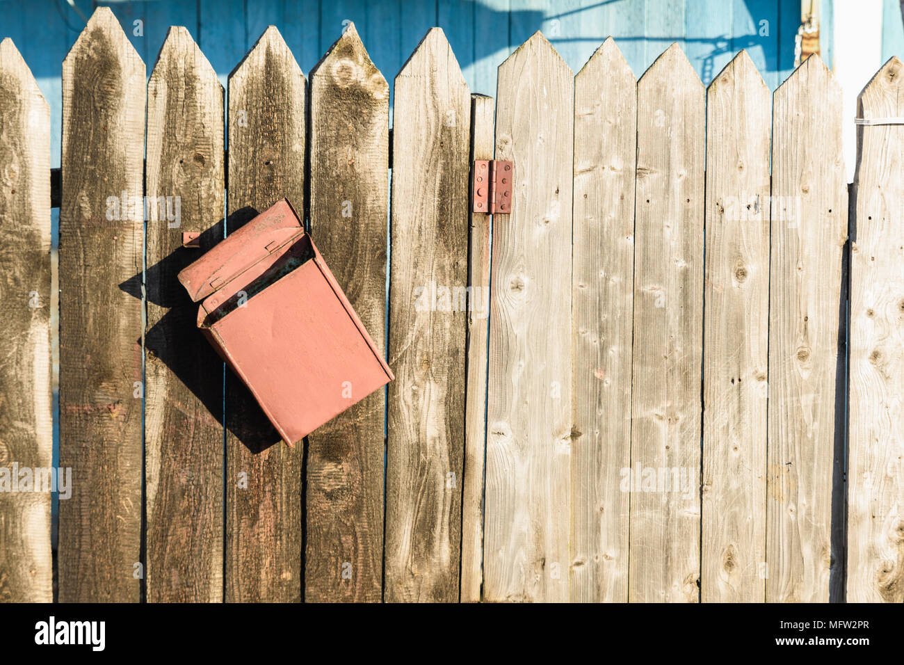old wooden fence and a crooked rusty letter box Stock Photo