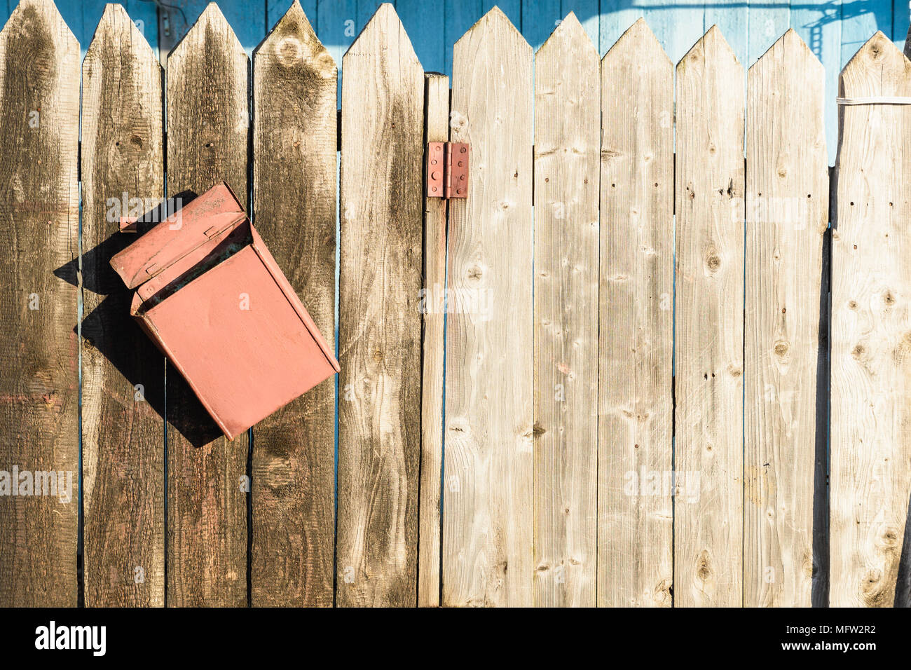 old wooden fence and a crooked rusty letter box - Stock Image
