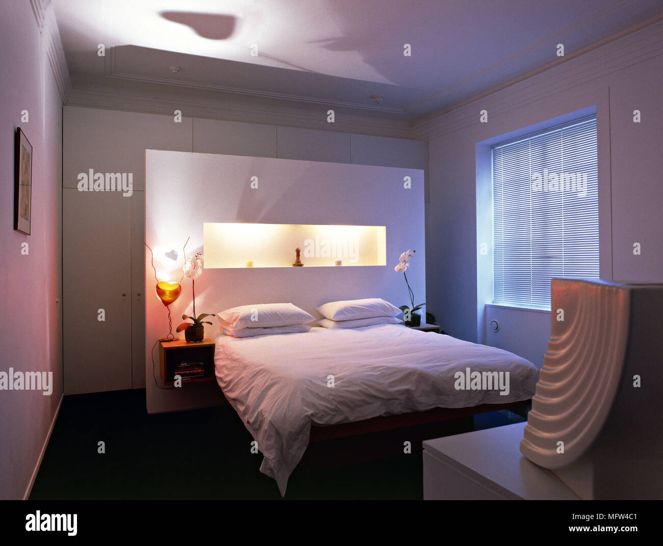 A modern bedroom with double bed lit alcove in freestanding wall ...