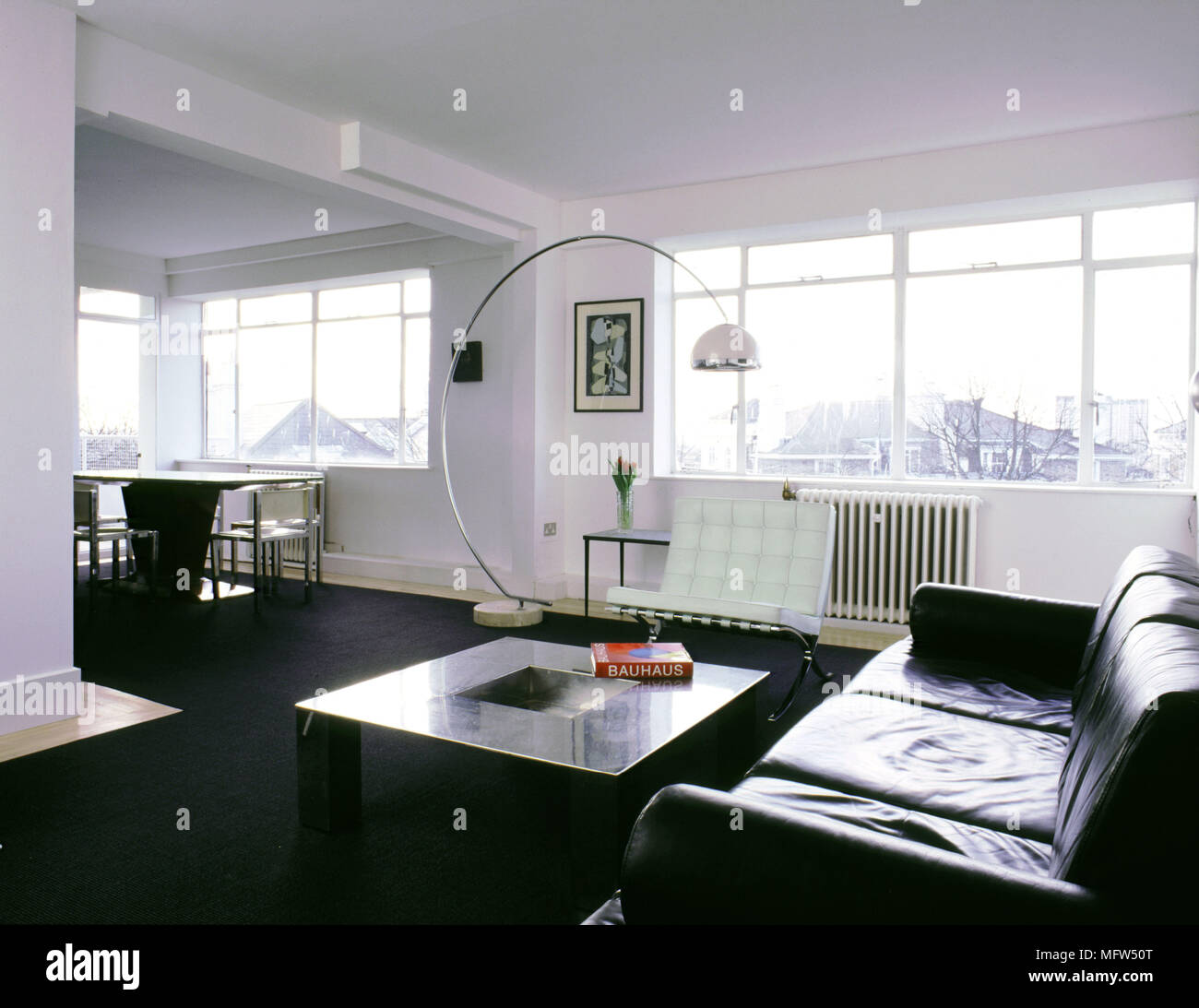 Modern Open Living Area With Black Carpet Dining Table And Chairs Leather Sofa Curving Floor Lamp Sunny Windows