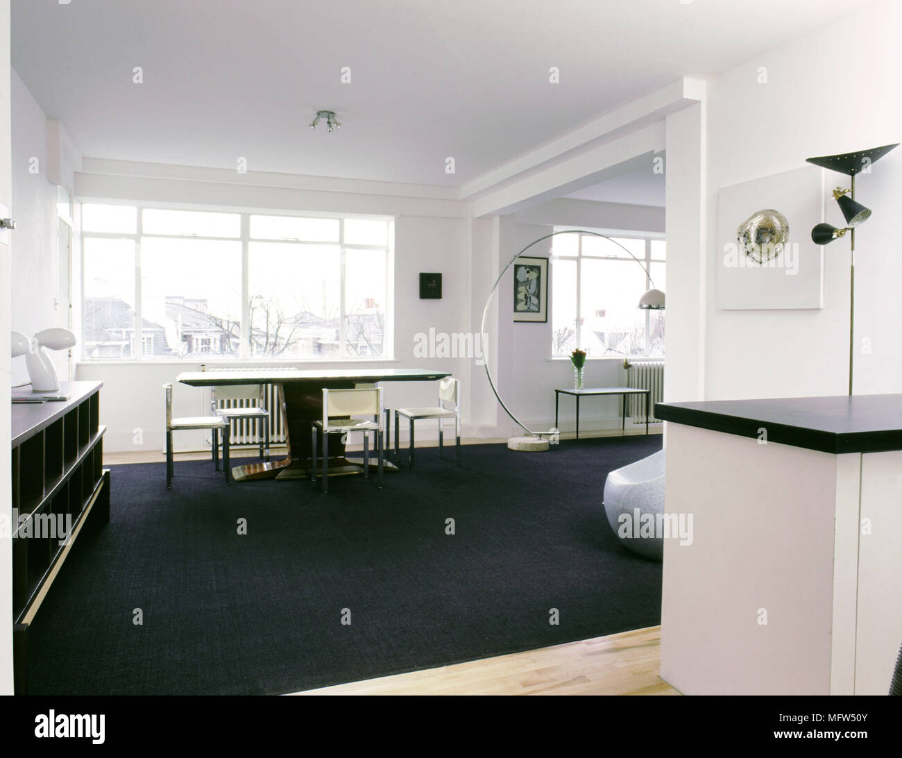 Modern Open Living Area With Black Carpet Dining Table And Chairs Curving Floor Lamp Sunny Windows