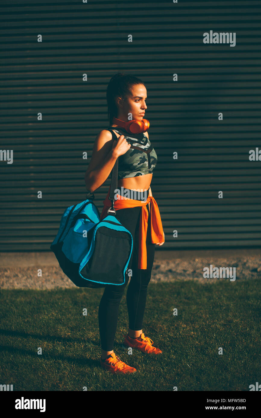 00dd7ed1 Young woman standing with sport bag outdoor after training Stock ...