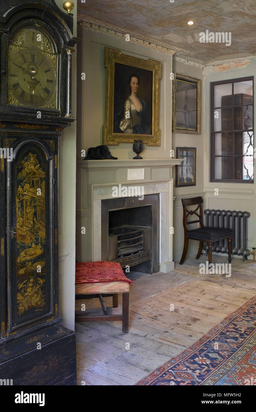 A detail of a traditional sitting room fireplace long case clock stripped floorboards - Stock Image