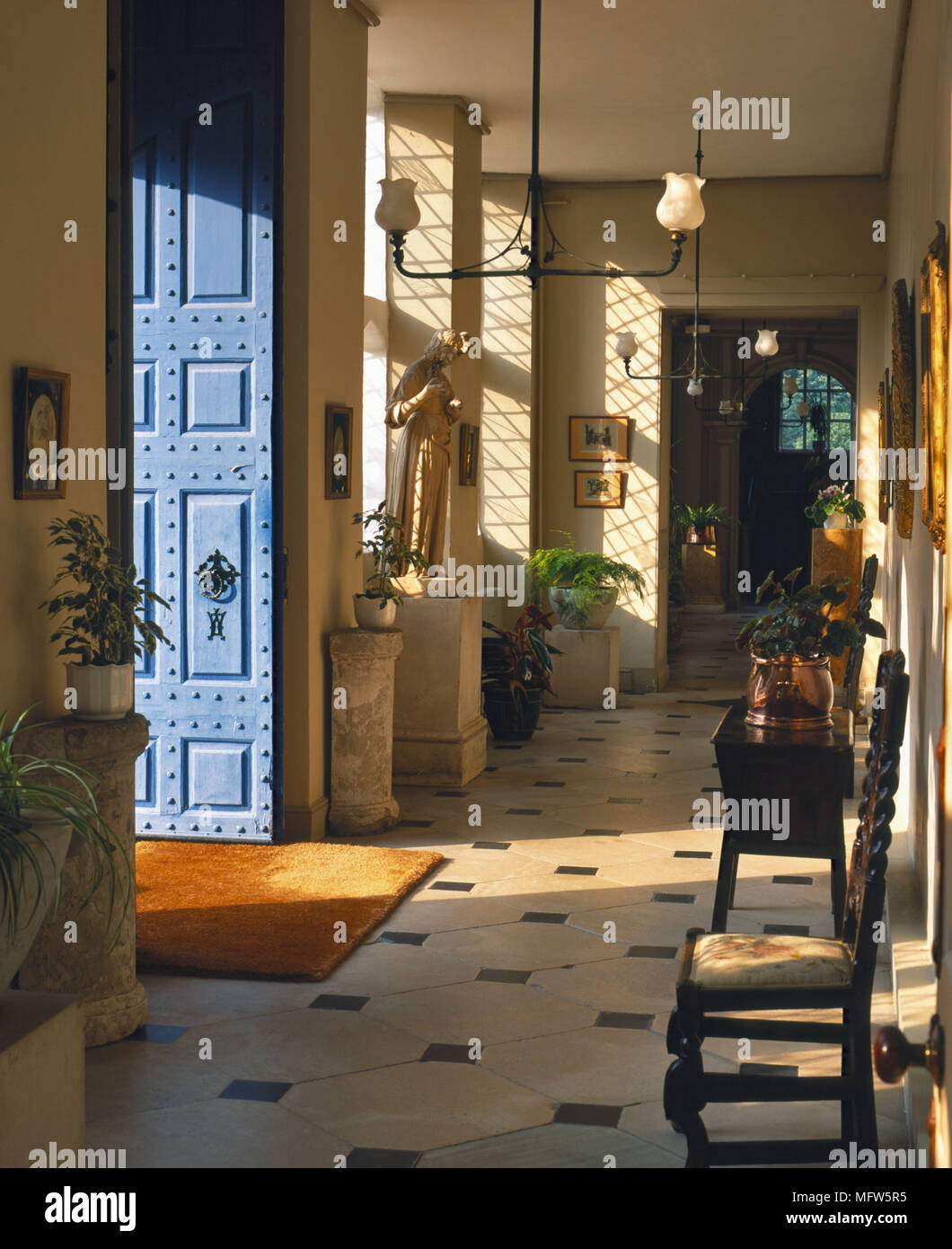 A traditional entrance hallway tiled floor door open Jacobean style wooden chair house plants Stock Photo