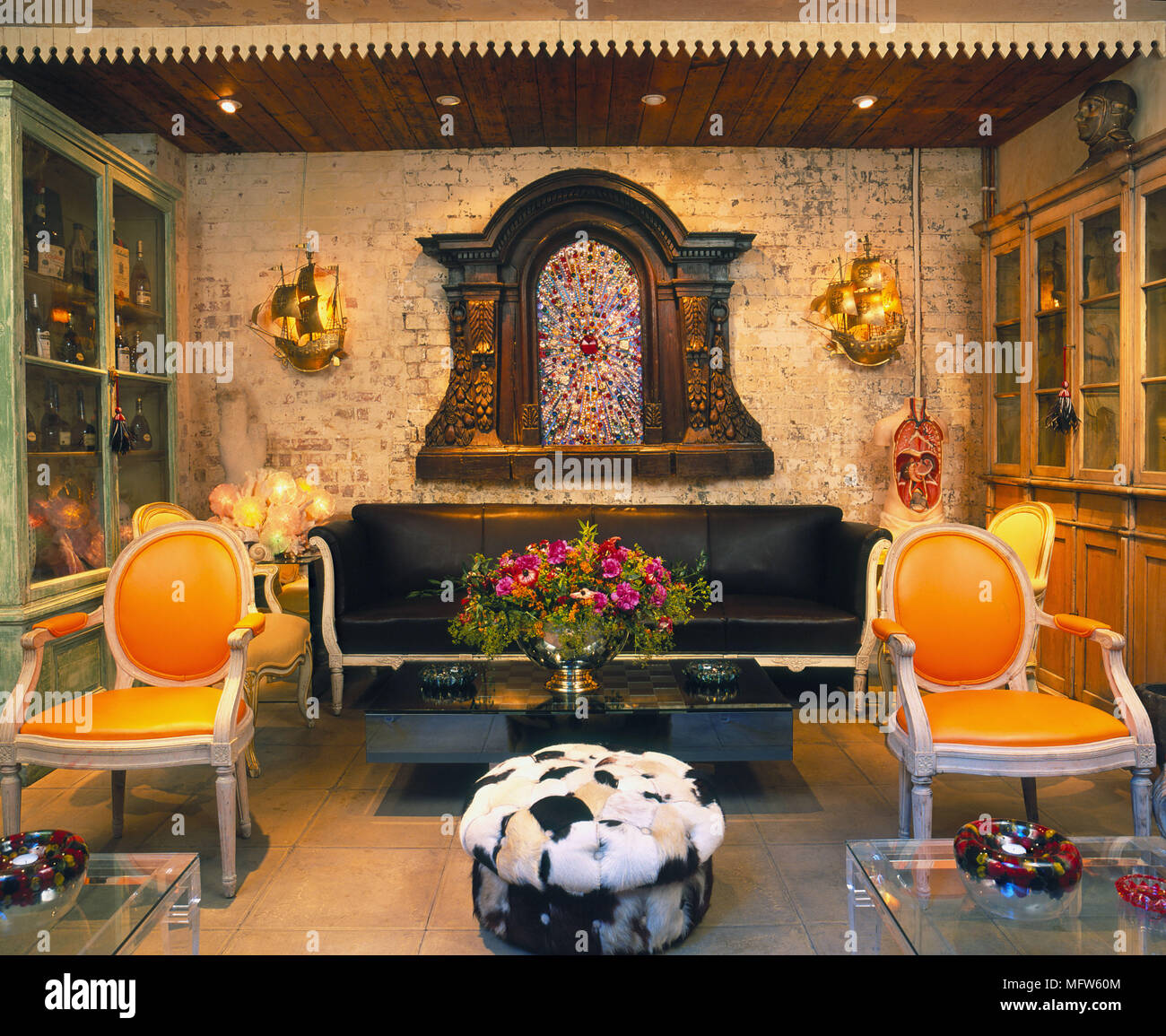Details Of A Bohemian Styled Sitting Room With Two Period Orange Chairs In  Front Of A Black Leather Couch With A Coffee Table With Flowers.