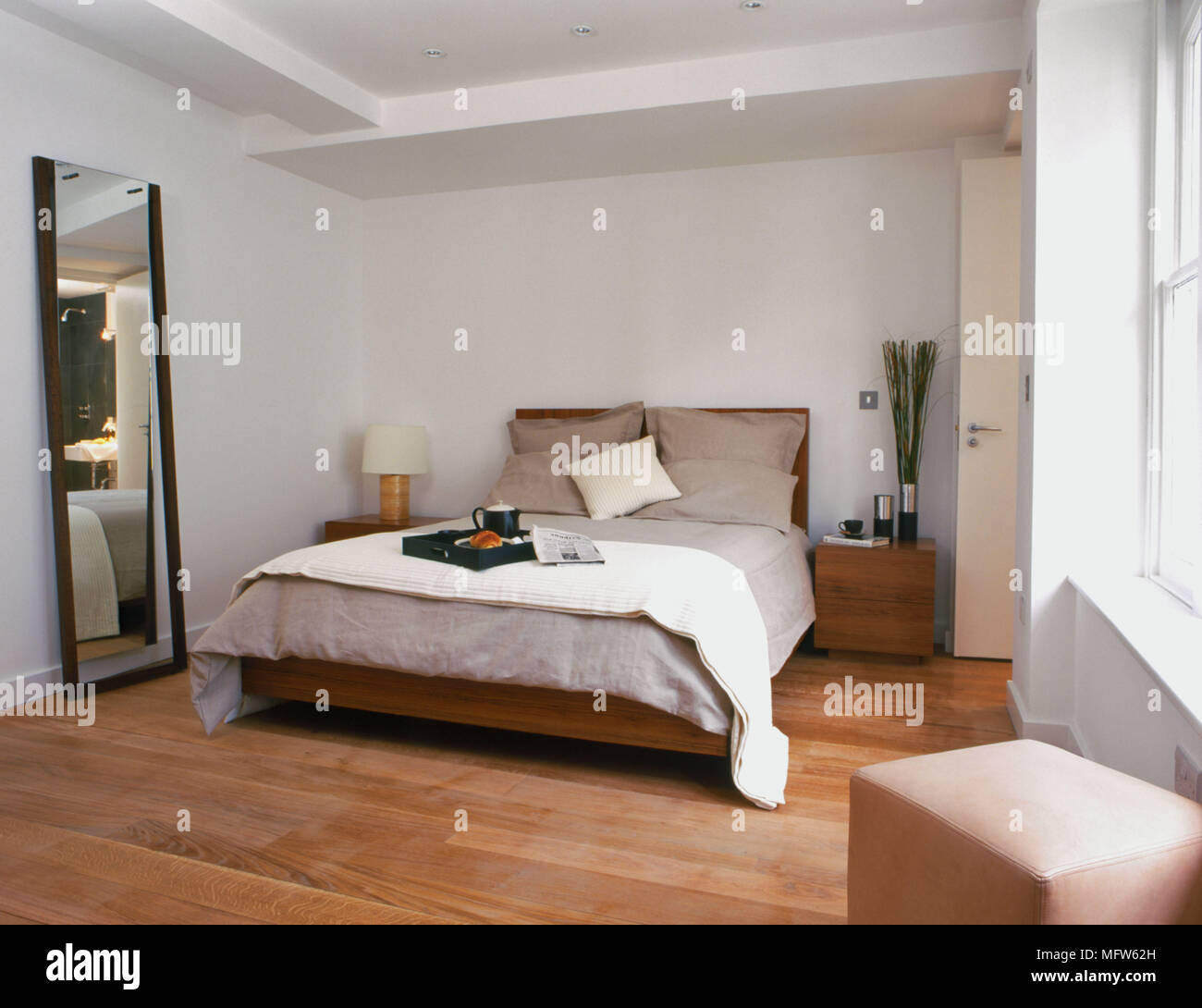 Details Of A Modern Bedroom With A Large Full Length Mirror Next To A Double Bed With Two Wooden Side Tables And A Square Seat In The Foreground Stock Photo Alamy