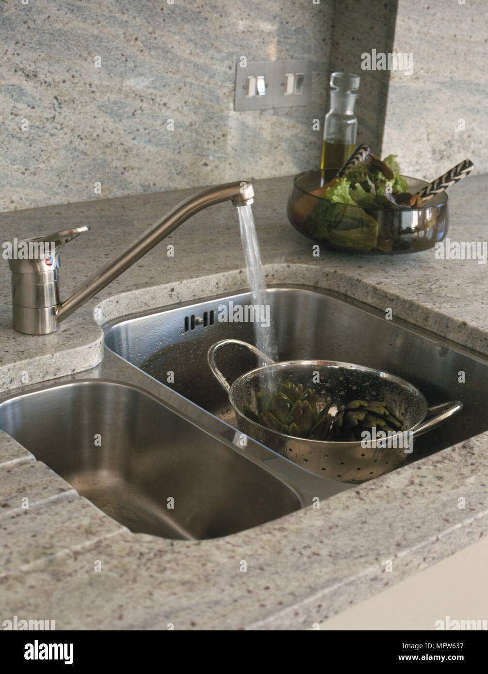 Details of a modern stainless steel kitchen sink with a colander ...