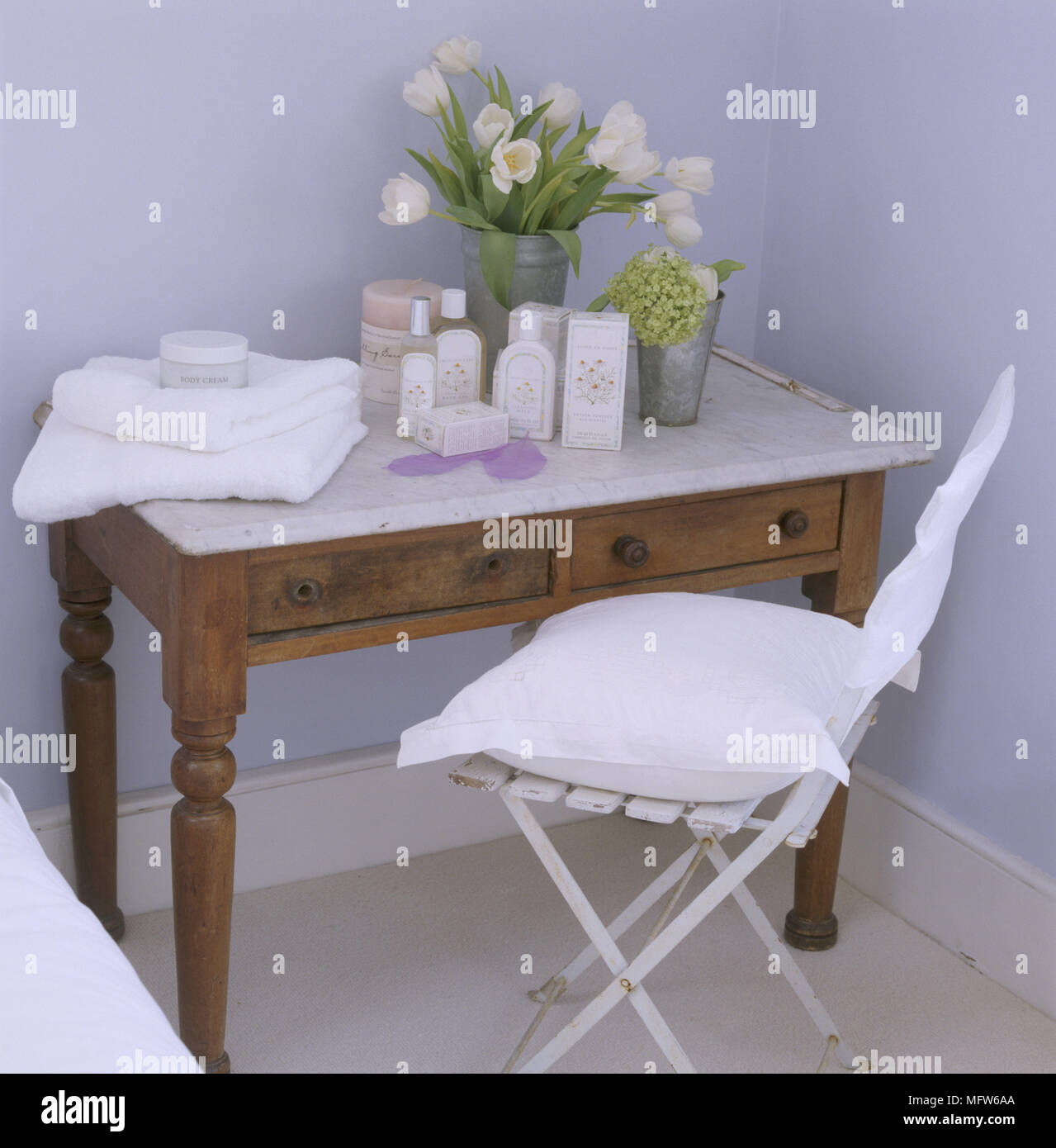 A Detail Of A Country Bedroom Showing A Wooden Wash Stand Table With Marble  Top And Painted Chair Tulip Flower Arrangement Toiletries