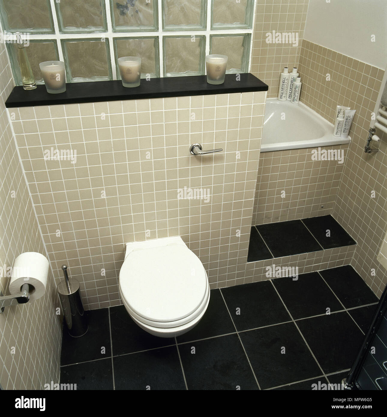 Bathroom with mosaic tiling and wall mounted toilet and bathtub and ...