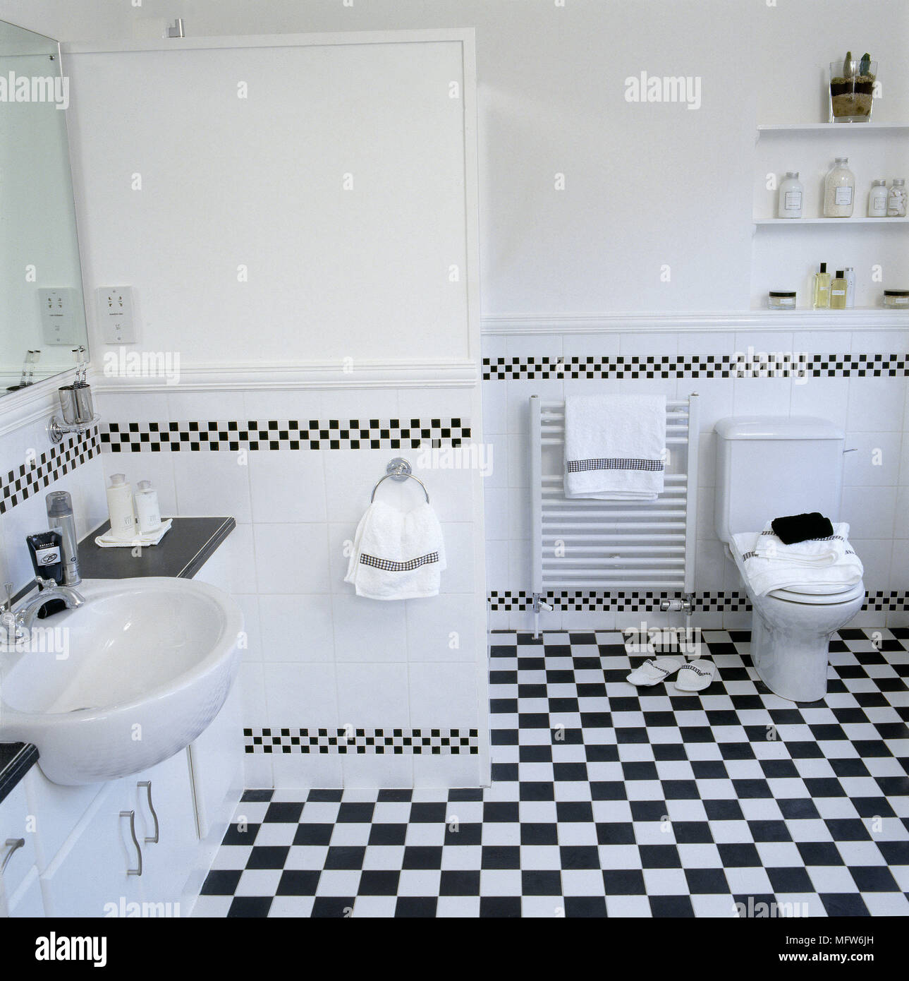 Modern bathroom with black and white chequered tile sink toilet and ...
