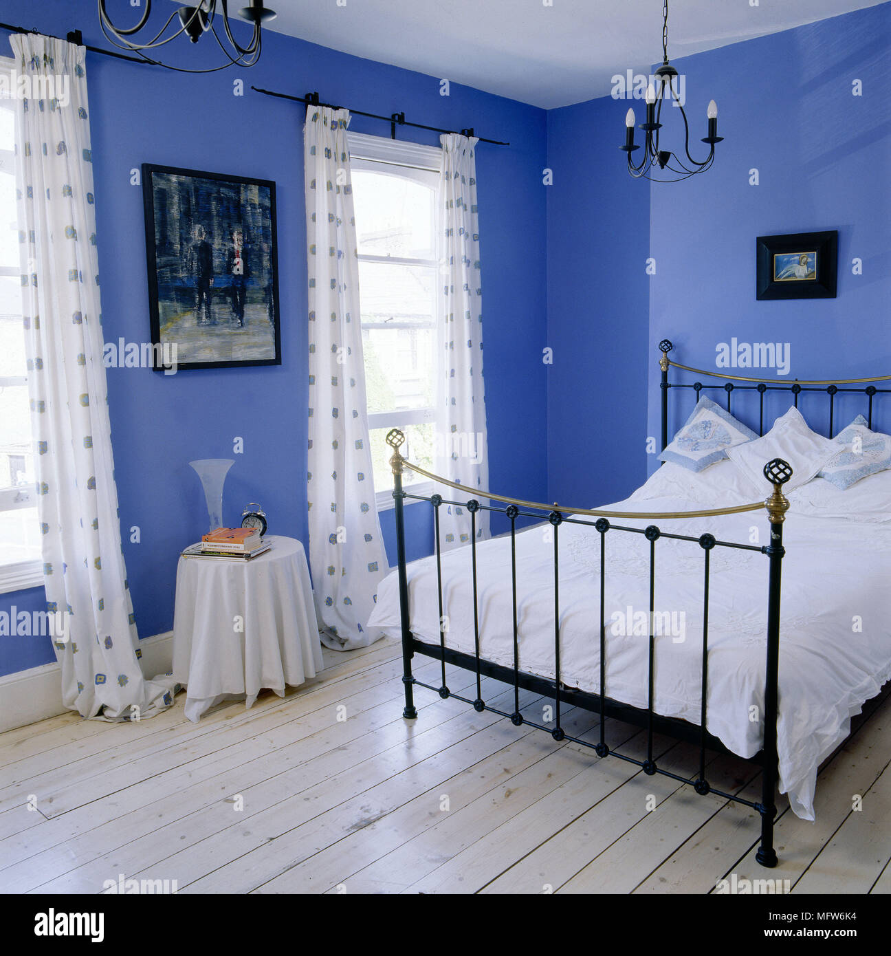 Modern Blue Bedroom With Stripped Floorboards Black Wrought Iron Bed And Patterned Curtains Stock Photo Alamy
