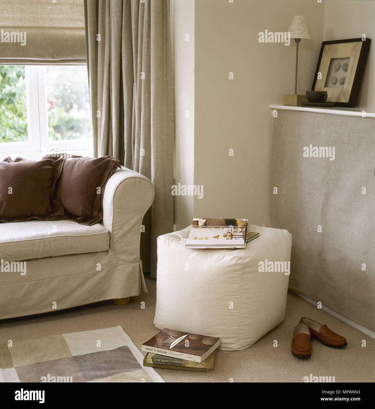 Upholstered sofa and ottoman in sitting room in neutral colours - Stock Image