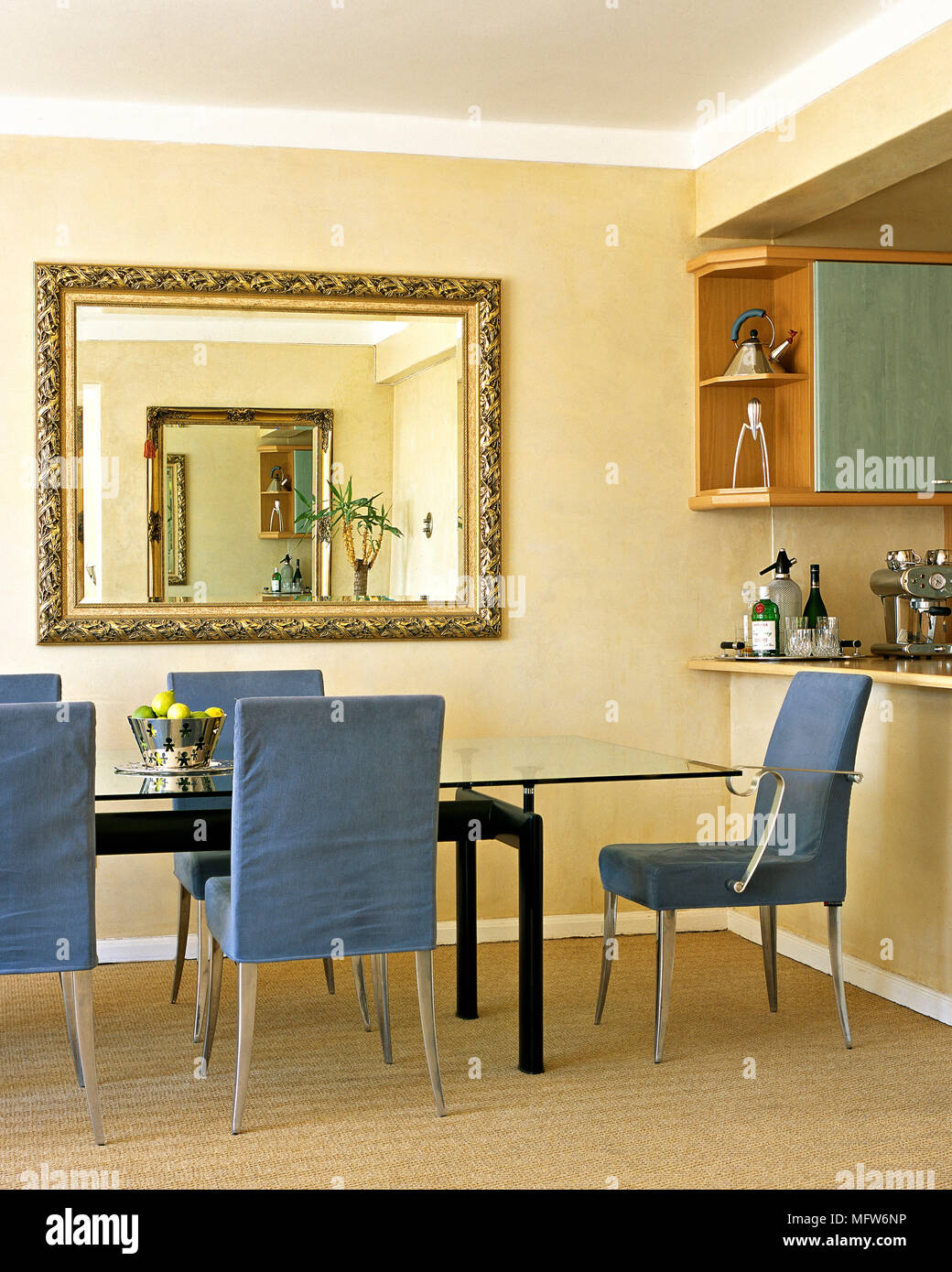 A Modern Open Plan Kitchen With Dining Area Glass Table Blue Covered Chairs Gilt Mirror Stock Photo Alamy