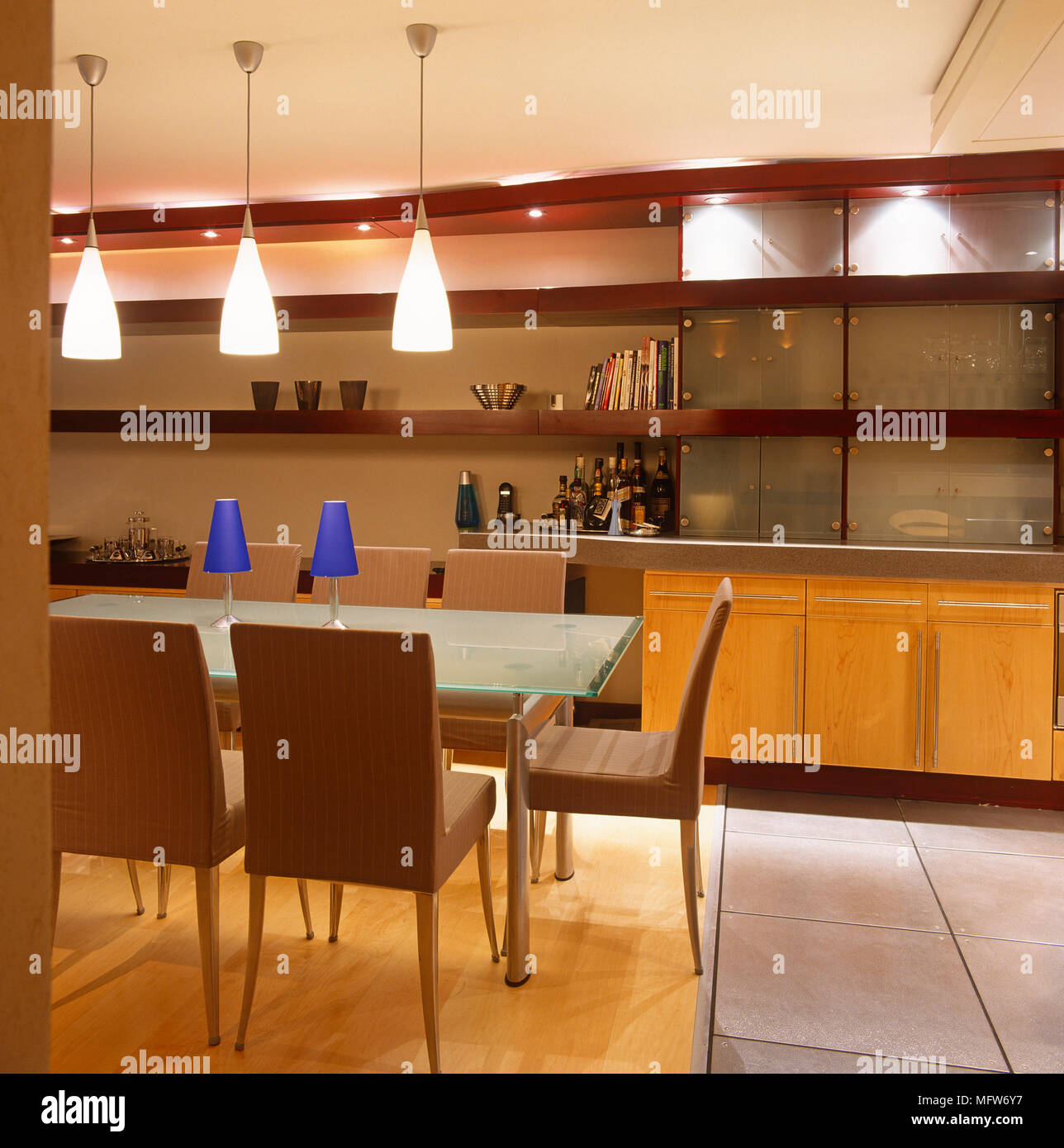Three Ceiling Lights Suspended Above Glass Dining Table Stock Photo Alamy