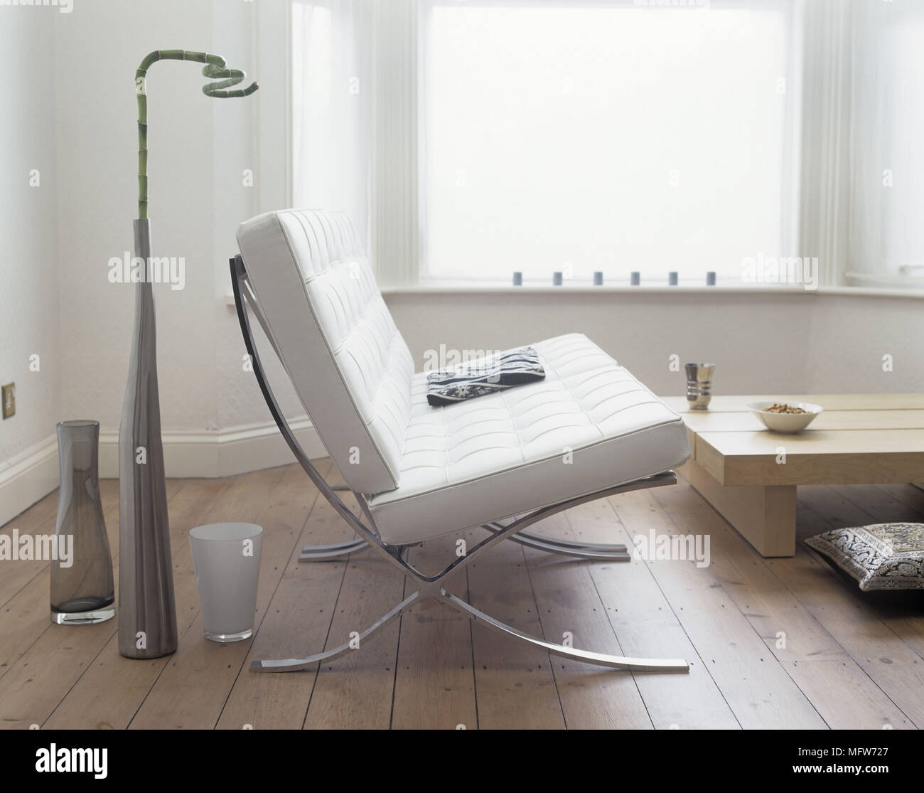 A detail of a modern white sitting room a white leather Barcelona chair by Mies van der Rohe wooden floor glass vases low wooden coffee table & A detail of a modern white sitting room a white leather Barcelona ...