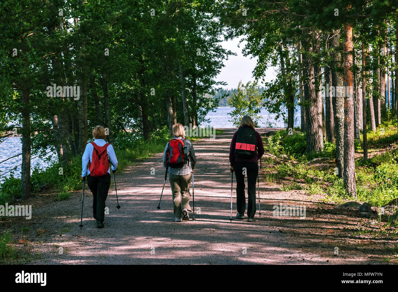 Three women with backpacks and walking sticks make a promenade along the sandy path along the shore of Lake Saimaa in the Finnish city of Imatra. Stock Photo