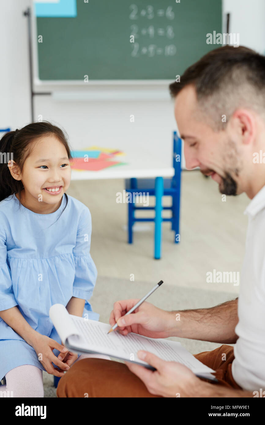 Male primary school teacher writing something on clipboard while giving private lesson to cheerful Asian girl sitting next to him - Stock Image