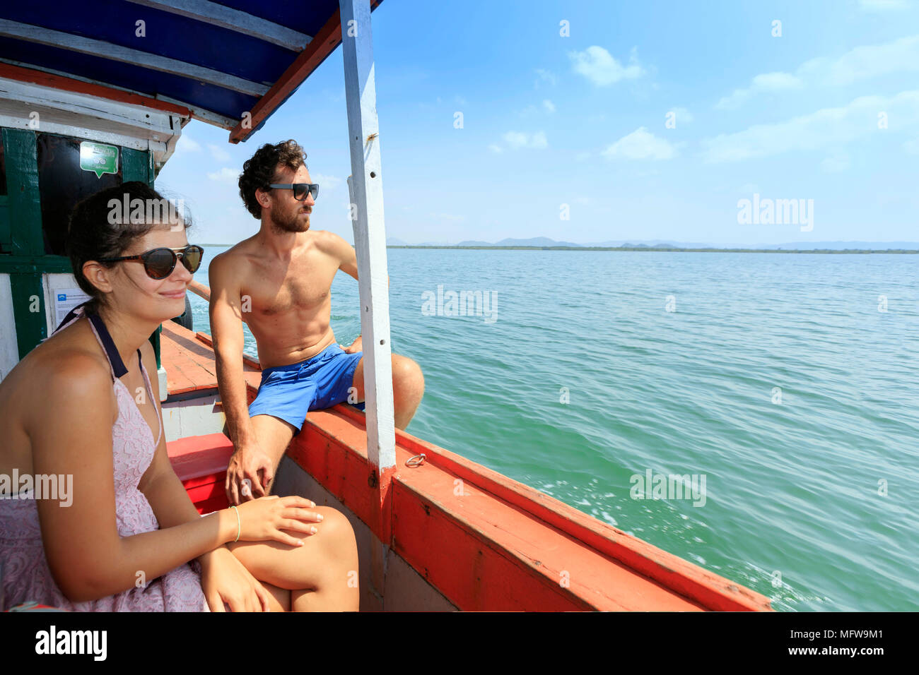 Young travelers on a boat to the islands of Cambodia, looking out over the water on a sunny day. Copy space to the right for a double-page spread. - Stock Image