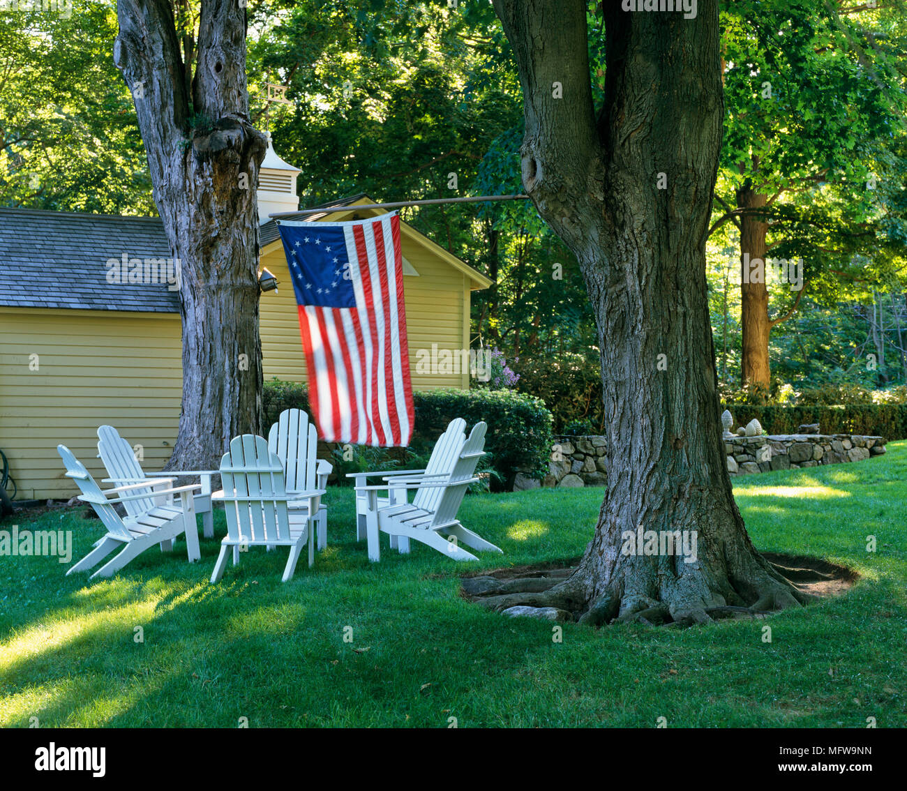 Adirondack chairs in garden amongst trees with American flag - Stock Image