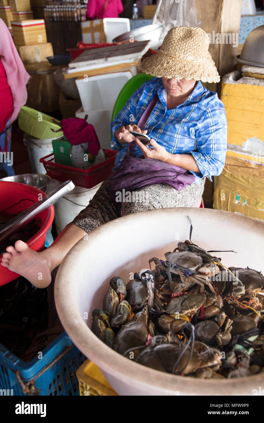 Cham woman in a straw hat selling crabs in Kep crab market - Stock Image