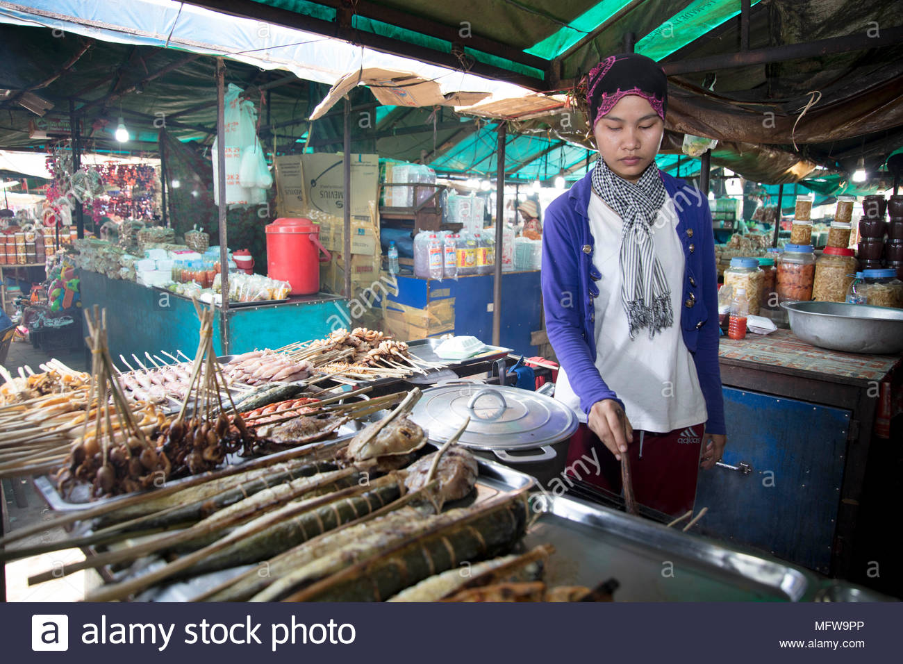 Young Cham woman grilling fish at a stall in the Crab Market in Kep village, Cambodia - Stock Image