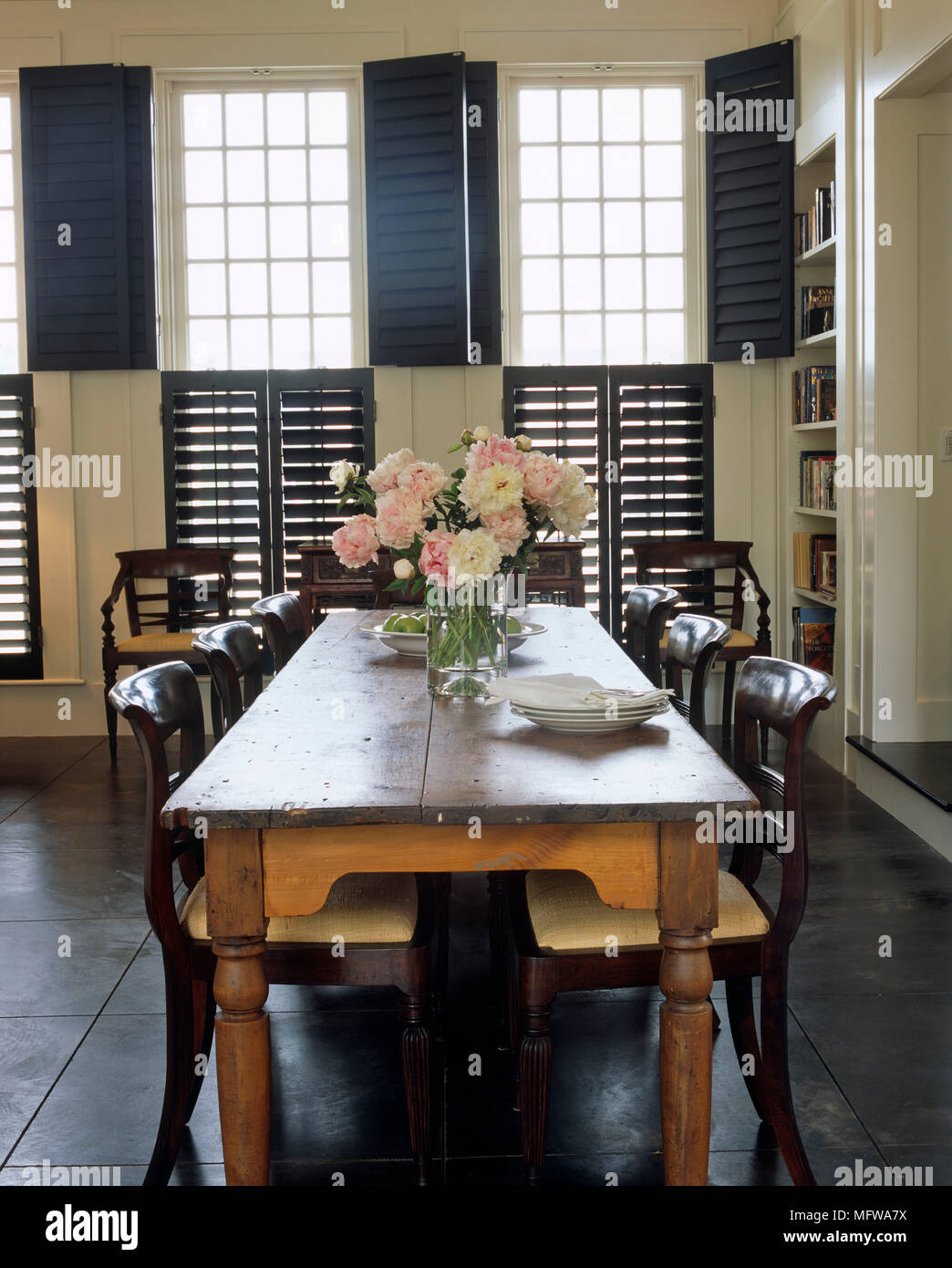 Picture of: Dining Room With Long Wooden Table And Chairs In Front Of Window With Shutters Stock Photo Alamy