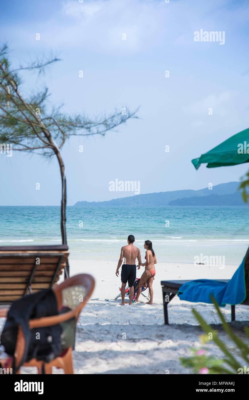 Candid shot of a young couple talking on a white sand beach on an island in Southeast Asia - Stock Image