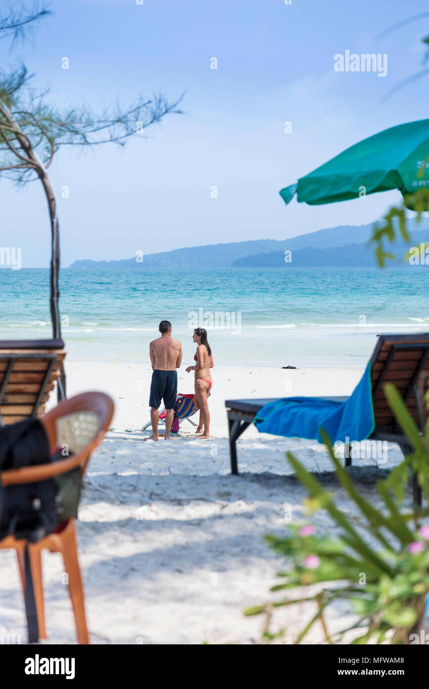 Candid shot of a young couple talking on a white sand beach on an island in Southeast Asia Stock Photo